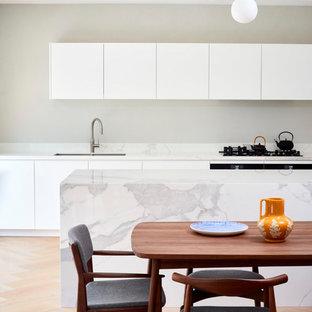 Esempio di una cucina minimal di medie dimensioni con lavello sottopiano, ante a persiana, ante bianche, top in marmo, paraspruzzi bianco, paraspruzzi in marmo, elettrodomestici da incasso, isola e top bianco
