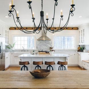 Idéer för ett stort lantligt kök, med en rustik diskho, luckor med profilerade fronter, vita skåp, marmorbänkskiva, vitt stänkskydd, stänkskydd i sten, rostfria vitvaror, mellanmörkt trägolv och en köksö