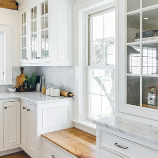 Large country u-shaped eat-in kitchen in New York with a farmhouse sink, beaded inset cabinets, white cabinets, marble benchtops, white splashback, stone slab splashback, stainless steel appliances, medium hardwood floors and with island.