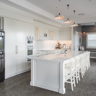 Photo of a transitional u-shaped eat-in kitchen in Sunshine Coast with a farmhouse sink, shaker cabinets, white cabinets, quartz benchtops, white splashback, subway tile splashback, stainless steel appliances, with island, grey floor and white benchtop.