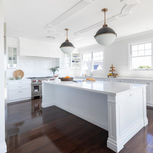 Photo of a transitional u-shaped kitchen in Brisbane with white cabinets, quartz benchtops, white splashback, subway tile splashback, dark hardwood floors, with island, white benchtop, shaker cabinets, stainless steel appliances and brown floor.
