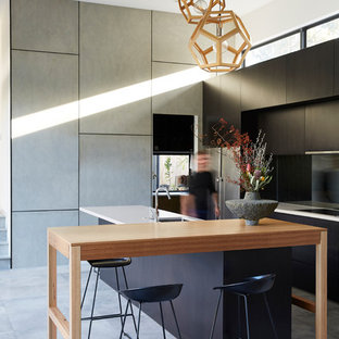 Design ideas for a contemporary galley eat-in kitchen in Brisbane with an undermount sink, flat-panel cabinets, black cabinets, black splashback, panelled appliances, with island, grey floor, porcelain floors and white benchtop.