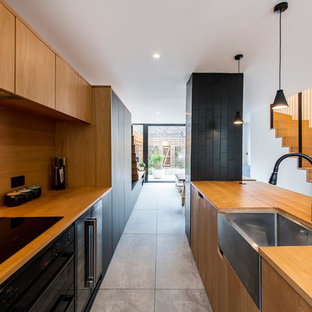 Inspiration for a scandinavian kitchen in Sussex with a belfast sink, flat-panel cabinets, medium wood cabinets, wood worktops, wood splashback, black appliances and grey floors.