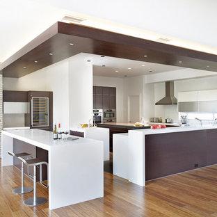 Modelo de cocina en L, moderna, grande, abierta, con electrodomésticos de acero inoxidable, armarios con paneles lisos, puertas de armario marrones, encimera de cuarzo compacto, suelo de madera en tonos medios, una isla y suelo marrón