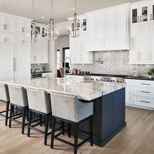 Источник вдохновения для домашнего уюта: угловая кухня-гостиная в стиле неоклассика (современная классика) с раковиной в стиле кантри, фасадами в стиле шейкер, белыми фасадами, фартуком из плитки кабанчик, техникой под мебельный фасад, паркетным полом среднего тона, островом, коричневым полом и черной столешницей