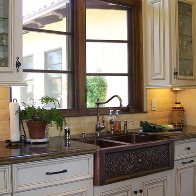 Inspiration for a large timeless l-shaped ceramic tile and beige floor open concept kitchen remodel in San Diego with raised-panel cabinets, a farmhouse sink, marble countertops, white cabinets, beige backsplash, stone tile backsplash, stainless steel appliances and two islands