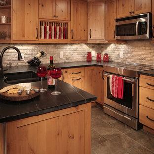 デンバーのラスティックスタイルのおしゃれなキッチン (アンダーカウンターシンク、シェーカースタイル扉のキャビネット、ソープストーンカウンター、ベージュキッチンパネル、石タイルのキッチンパネル、シルバーの調理設備の、磁器タイルの床) の写真