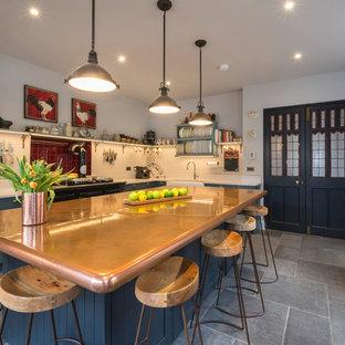 Удачное сочетание для дизайна помещения: угловая кухня в викторианском стиле с раковиной в стиле кантри, фасадами в стиле шейкер, синими фасадами, столешницей из меди, цветной техникой, островом и серым полом - самое интересное для вас