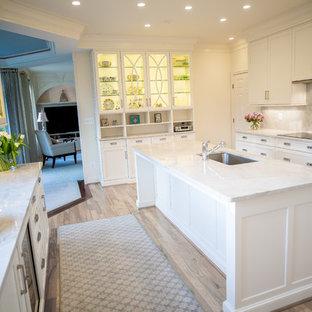 ワシントンD.C.の広いヴィクトリアン調のおしゃれなキッチン (ドロップインシンク、白いキャビネット、ベージュキッチンパネル、シルバーの調理設備、淡色無垢フローリング、茶色い床、シェーカースタイル扉のキャビネット、クオーツストーンカウンター) の写真