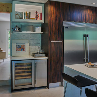 Eat-in kitchen - mid-sized modern l-shaped concrete floor and gray floor eat-in kitchen idea in Miami with flat-panel cabinets, dark wood cabinets, quartz countertops, gray backsplash, matchstick tile backsplash, stainless steel appliances, a peninsula and white countertops