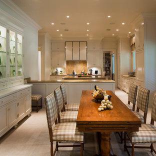 Zweizeilige, Große Klassische Wohnküche mit Schrankfronten mit vertiefter Füllung, weißen Schränken, Küchenrückwand in Braun, Rückwand aus Stein, Elektrogeräten mit Frontblende, Travertin, Kücheninsel und beigem Boden in Miami