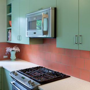 Inspiration for a small transitional u-shaped eat-in kitchen in Portland with an undermount sink, flat-panel cabinets, green cabinets, recycled glass benchtops, orange splashback, ceramic splashback, stainless steel appliances and light hardwood floors.