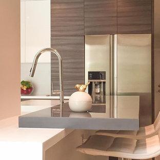 マイアミの中サイズのモダンスタイルのおしゃれなキッチン (人工大理石カウンター、一体型シンク、フラットパネル扉のキャビネット、中間色木目調キャビネット、白いキッチンパネル、石スラブのキッチンパネル、シルバーの調理設備の、セラミックタイルの床、ベージュの床、グレーのキッチンカウンター) の写真