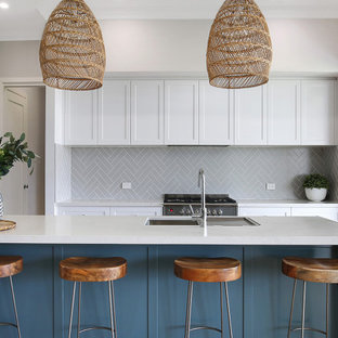 Photo of a mid-sized beach style kitchen in Wollongong with white cabinets, quartz benchtops, subway tile splashback, with island and white benchtop.