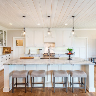 Example of a classic l-shaped medium tone wood floor and brown floor kitchen design in Other with a farmhouse sink, shaker cabinets, white cabinets, white backsplash, subway tile backsplash, stainless steel appliances, an island and gray countertops
