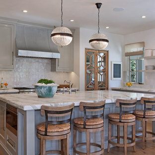 Traditional kitchen remodeling - Elegant l-shaped medium tone wood floor and brown floor kitchen photo in Los Angeles with beaded inset cabinets, gray cabinets, white backsplash, stainless steel appliances and an island