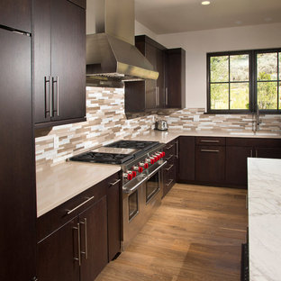Mid-sized modern eat-in kitchen appliance - Mid-sized minimalist l-shaped light wood floor and beige floor eat-in kitchen photo in Denver with an undermount sink, flat-panel cabinets, dark wood cabinets, granite countertops, beige backsplash, stone tile backsplash, paneled appliances and an island