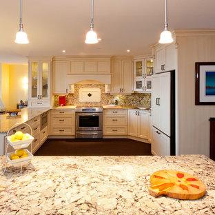 Idéer för ett mellanstort klassiskt beige kök, med en undermonterad diskho, luckor med infälld panel, vita skåp, granitbänkskiva, beige stänkskydd, stänkskydd i sten, rostfria vitvaror, heltäckningsmatta, en köksö och brunt golv