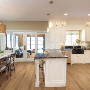 Mid-sized contemporary eat-in kitchen ideas - Example of a mid-sized trendy l-shaped vinyl floor and beige floor eat-in kitchen design in Sacramento with a farmhouse sink, shaker cabinets, white cabinets, granite countertops, white backsplash, stone tile backsplash, stainless steel appliances and a peninsula
