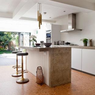 Inredning av ett modernt stort beige beige parallellkök, med släta luckor, vita skåp, rostfria vitvaror, en köksö och orange golv