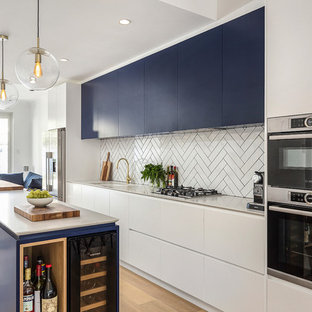 This is an example of a large contemporary galley open plan kitchen in Sydney with an undermount sink, flat-panel cabinets, blue cabinets, white splashback, subway tile splashback, light hardwood floors, with island, white benchtop, quartz benchtops, stainless steel appliances and brown floor.