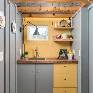 ナッシュビルのインダストリアルスタイルのおしゃれなI型キッチン (ドロップインシンク、フラットパネル扉のキャビネット、黄色いキャビネット、木材カウンター、白いキッチンパネル、濃色無垢フローリング、アイランドなし、茶色い床、茶色いキッチンカウンター) の写真