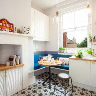 ロンドンの小さいエクレクティックスタイルのおしゃれなL型キッチン (フラットパネル扉のキャビネット、白いキャビネット、ドロップインシンク、白いキッチンパネル、サブウェイタイルのキッチンパネル、アイランドなし、マルチカラーの床) の写真