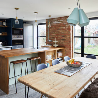 Inspiration for a country galley kitchen/diner in Surrey with a submerged sink, shaker cabinets, blue cabinets, wood worktops, stainless steel appliances, a breakfast bar, grey floors and brown worktops.