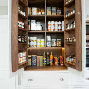 This is an example of a classic kitchen pantry in Berkshire with shaker cabinets, white cabinets and concrete flooring.