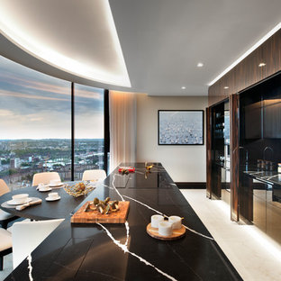 This is an example of a large contemporary single-wall enclosed kitchen in London with an integrated sink, recessed-panel cabinets, dark wood cabinets, marble worktops, black splashback, marble splashback, stainless steel appliances, marble flooring, an island, white floors and black worktops.