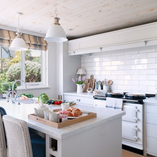 This is an example of a nautical galley kitchen in Cornwall with grey cabinets, white splashback, ceramic splashback, white appliances, medium hardwood flooring, brown floors, white worktops, a submerged sink, flat-panel cabinets and a breakfast bar.