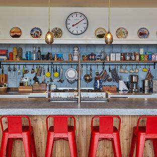 コーンウォールの大きいエクレクティックスタイルのおしゃれなキッチン (アンダーカウンターシンク、コンクリートカウンター、青いキッチンパネル、セラミックタイルのキッチンパネル、シルバーの調理設備の、グレーのキッチンカウンター) の写真
