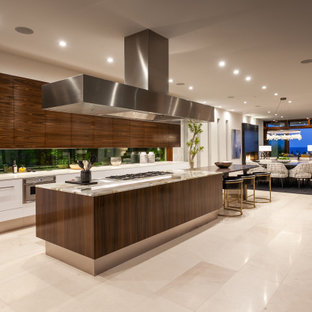 Geräumige Moderne Küche in L-Form mit Unterbauwaschbecken, flächenbündigen Schrankfronten, hellbraunen Holzschränken, Küchengeräten aus Edelstahl, Porzellan-Bodenfliesen, Kücheninsel, beigem Boden und beiger Arbeitsplatte in Orange County