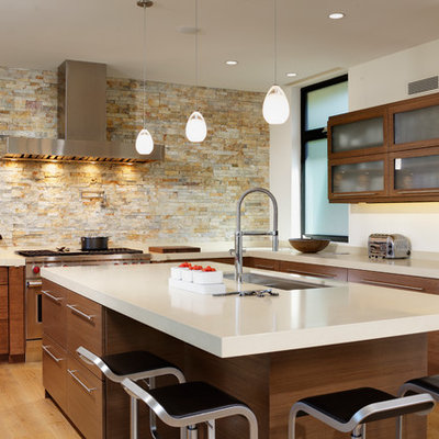 Inspiration for a large contemporary u-shaped light wood floor open concept kitchen remodel in Orange County with flat-panel cabinets, medium tone wood cabinets, paneled appliances, an undermount sink, quartzite countertops, beige backsplash, an island and limestone backsplash