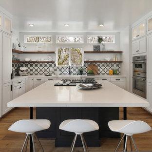 Bild på ett mellanstort funkis vit vitt u-kök, med en rustik diskho, skåp i shakerstil, vita skåp, bänkskiva i kvarts, flerfärgad stänkskydd, stänkskydd i cementkakel, integrerade vitvaror, mellanmörkt trägolv, en köksö och brunt golv