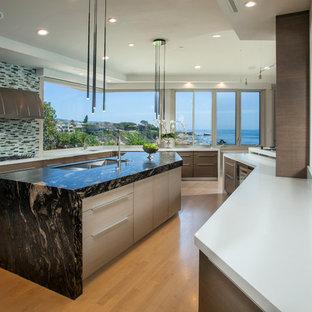 Идея дизайна: большая кухня в современном стиле с обеденным столом, тройной раковиной, плоскими фасадами, светлыми деревянными фасадами, зеленым фартуком, фартуком из плитки мозаики, техникой из нержавеющей стали, светлым паркетным полом и островом