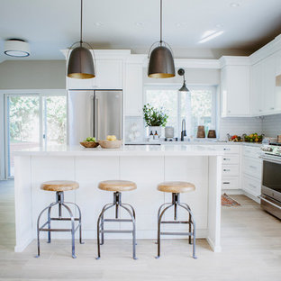 Photo of a mid-sized beach style l-shaped open plan kitchen in San Diego with an undermount sink, shaker cabinets, white cabinets, quartz benchtops, white splashback, subway tile splashback, stainless steel appliances, ceramic floors, with island and brown floor.