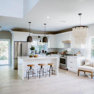 This is an example of a mid-sized beach style l-shaped open plan kitchen in San Diego with an undermount sink, shaker cabinets, white cabinets, quartz benchtops, white splashback, subway tile splashback, stainless steel appliances, ceramic floors, with island and brown floor.