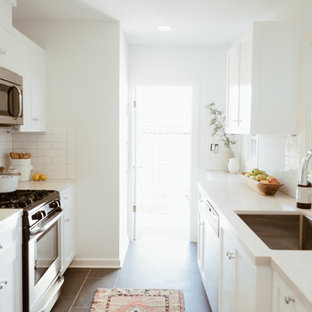 Inspiration for a small beach style galley separate kitchen in San Diego with an undermount sink, shaker cabinets, white cabinets, quartz benchtops, white splashback, subway tile splashback, stainless steel appliances, ceramic floors and no island.