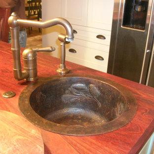 サンディエゴの中くらいのトラディショナルスタイルのおしゃれなキッチン (エプロンフロントシンク、シェーカースタイル扉のキャビネット、緑のキャビネット、木材カウンター、白いキッチンパネル、セラミックタイルのキッチンパネル、シルバーの調理設備、レンガの床、赤い床) の写真