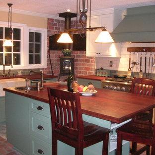 サンディエゴの中くらいのカントリー風おしゃれなキッチン (エプロンフロントシンク、シェーカースタイル扉のキャビネット、緑のキャビネット、木材カウンター、白いキッチンパネル、セラミックタイルのキッチンパネル、シルバーの調理設備、レンガの床、赤い床) の写真