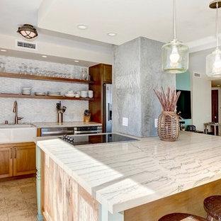 サンディエゴのビーチスタイルのおしゃれなキッチン (エプロンフロントシンク、シェーカースタイル扉のキャビネット、中間色木目調キャビネット、珪岩カウンター、白いキッチンパネル、大理石の床、シルバーの調理設備の、ライムストーンの床、ベージュの床) の写真