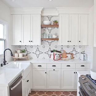 サンディエゴの小さい地中海スタイルのおしゃれなキッチン (エプロンフロントシンク、シェーカースタイル扉のキャビネット、中間色木目調キャビネット、クオーツストーンカウンター、マルチカラーのキッチンパネル、セラミックタイルのキッチンパネル、シルバーの調理設備、テラコッタタイルの床) の写真