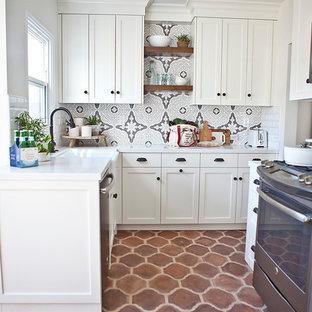 Идея дизайна: маленькая отдельная, п-образная кухня в средиземноморском стиле с раковиной в стиле кантри, фасадами в стиле шейкер, фасадами цвета дерева среднего тона, столешницей из кварцевого агломерата, разноцветным фартуком, фартуком из керамической плитки, техникой из нержавеющей стали, полом из терракотовой плитки и островом