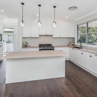 ブリスベンの中サイズのトラディショナルスタイルのおしゃれなキッチン (ダブルシンク、シェーカースタイル扉のキャビネット、白いキャビネット、クオーツストーンカウンター、ベージュキッチンパネル、セラミックタイルのキッチンパネル、黒い調理設備、茶色い床、ピンクのキッチンカウンター) の写真