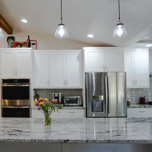 アルバカーキの中サイズのサンタフェスタイルのおしゃれなキッチン (エプロンフロントシンク、シェーカースタイル扉のキャビネット、白いキャビネット、御影石カウンター、グレーのキッチンパネル、セラミックタイルのキッチンパネル、シルバーの調理設備の、セラミックタイルの床、グレーの床、グレーのキッチンカウンター) の写真