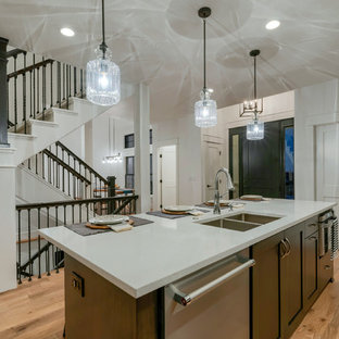 Inspiration for a mid-sized industrial single-wall open plan kitchen in Denver with a double-bowl sink, shaker cabinets, dark wood cabinets, quartz benchtops, brown splashback, brick splashback, stainless steel appliances, medium hardwood floors, with island, brown floor and white benchtop.