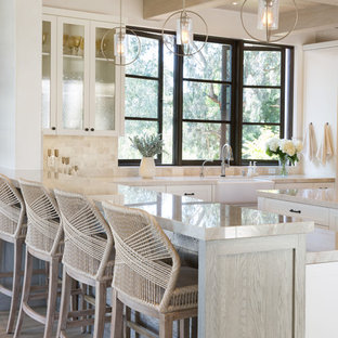 Photo of a large mediterranean l-shaped open plan kitchen in Santa Barbara with an undermount sink, shaker cabinets, white cabinets, quartzite benchtops, beige splashback, stone tile splashback, stainless steel appliances, light hardwood floors, with island, beige floor and beige benchtop.