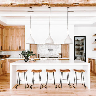 Farmhouse kitchen ideas - Inspiration for a farmhouse u-shaped medium tone wood floor and brown floor kitchen remodel in Phoenix with a farmhouse sink, shaker cabinets, medium tone wood cabinets, white backsplash, stainless steel appliances, an island and white countertops