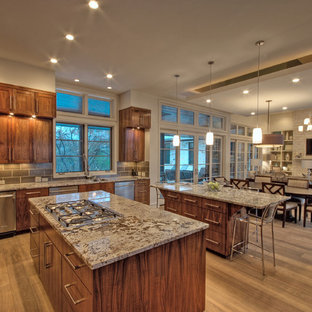 This is an example of a traditional open plan kitchen in Austin with recessed-panel cabinets, dark wood cabinets and stainless steel appliances.